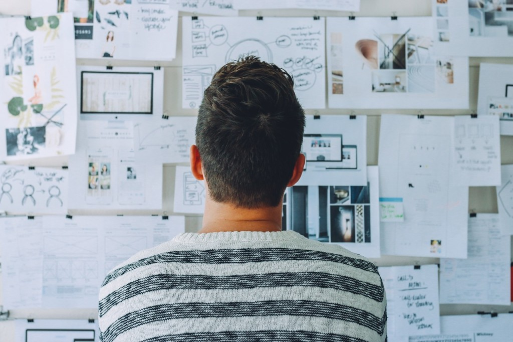 Homme réfléchi devant un mur rempli de papiers